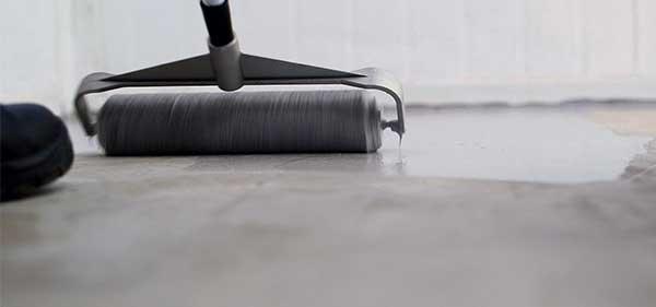 Photo d'un rouleau de peinture peignant un sol en béton gris
