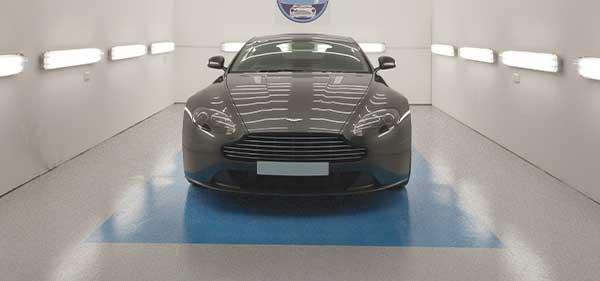 Photo d'une voiture dans un garage dont le sol est peint en gris et bleu.