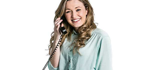 Photo d'une femme qui tient un téléphone filaire à son oreille sur fond blanc