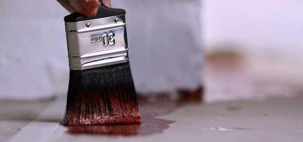 Photo d'un pinceau appliquant de la peinture rouge au sol