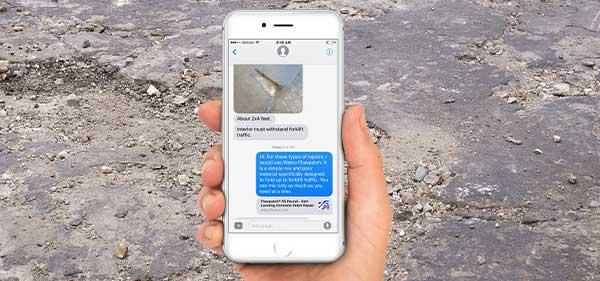 Photo d'une main tenant un iPhone dans lequel on peut voir une conversation avec un technicien Watco. Derrière l'iPhone, on peut voir un sol en béton endommagé.