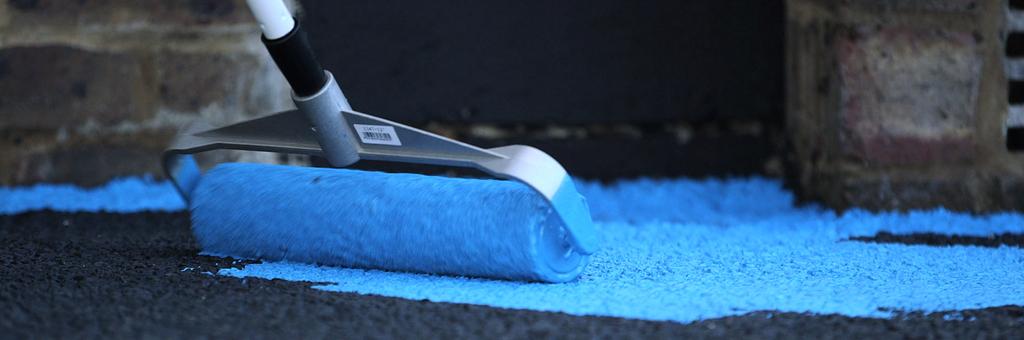 Photo d'un rouleau de peinture qui peint un sol noir avec de la peinture bleue